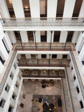 """Hotel Momentsin huoneisiin kuljetaan keskusaukiota ymräröiviltä """"parvilta""""."""