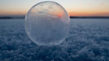 Jäätynyt saippukupla on kaunis yksityiskohta jäisellä jäälakeudella. Auringoslasku värittää taivaanrannan.