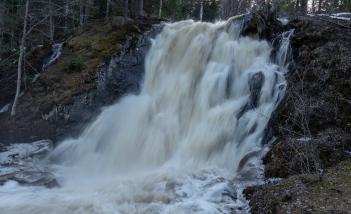 Vettä tulvi putouksesta leveänä seinänä kallionseinämää alaspäin.